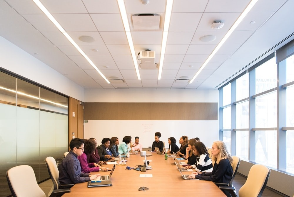 employees sitting inside a boardroom at the office